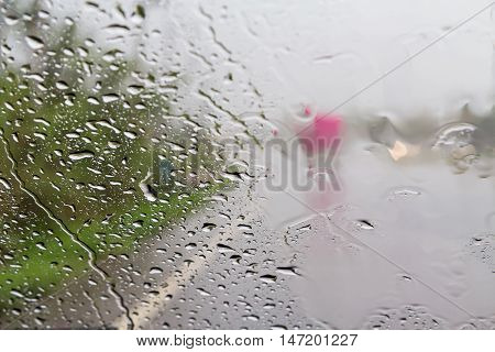 Road view through car windshield with rain drops Driving in rain.