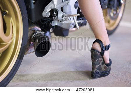 Girls leg in high wedge-heel is standing near bike.