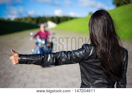 Hitchhiking Concept - Back View Of Woman Hitching Man On Motorcycle On The Road