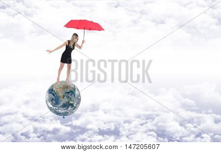 Barefoot girl on the planet earth represented as a balloon protects it with a red umbrella while flying away on the white clouds in a blue sky