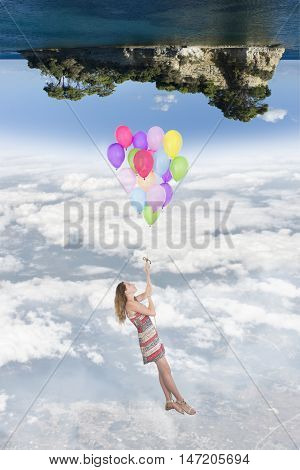 Girl hanging by a bunch of balloons flying toward a world upside down in the below there is the earth at the top there is an island in the sea