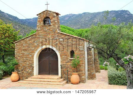 Quaint rustic stone Provencal chapel in france with terracotta pots among olive trees in France