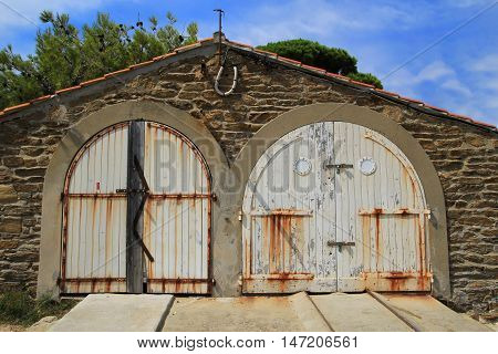 Rustic old provencal boat house with white wooden doors on a bright sunny day