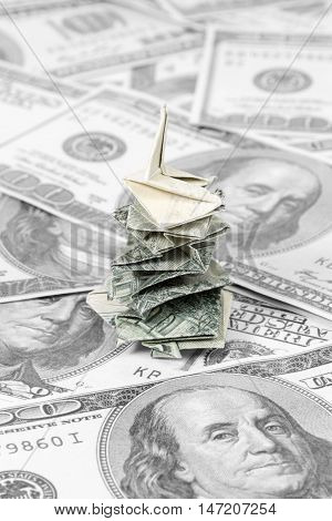Origami money tree made of dollars on a black and white background of hundred dollar banknotes