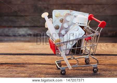 Shopping cart with pills, syringe on the old wood background. Toned image.