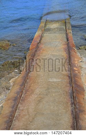 Rusty old iron and stone slipway leading from boathouse to the blue water
