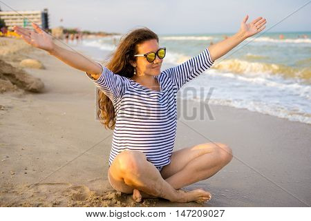 Woman on exotic beach in a striped sweater sitting with arms outstretched against turquoise sea. Carefree tourist is enjoying vacation at beach.