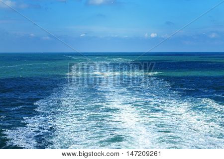 Wake of a ship on the ocean white foam in a blue sea under clear sky