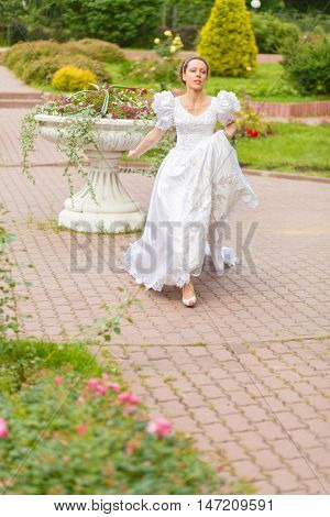 Full portrait of beautiful woman in white long dress running in summer park