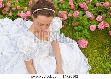 half length portrait of beautiful woman in white dress in summer park sitting on grass among flowers, above view