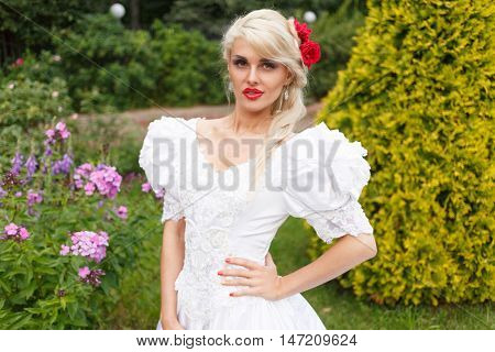 half length portrait of beautiful woman in white dress in summer park on background of shrubs and flowers