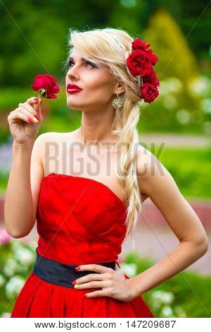 half length portrait of beautiful woman in red dress with rose in her hands in summer park, look throw