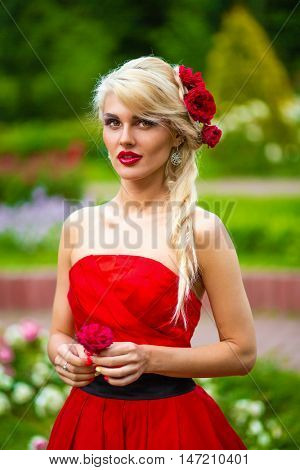 half length portrait of beautiful woman in red dress with rose in her hands in summer park