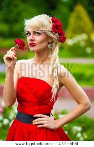 half length portrait of beautiful pretty woman in red dress with rose in her hands in summer park