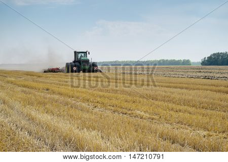 KRASNODAR REGION, RUSSIA - JUL 7, 2015: Modern tractor with plow plowing large field after harvest, In 2015 in Krasnodar region have collected record grain harvest - 102 million tons of grain