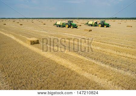KRASNODAR REGION, RUSSIA - JUL 7, 2015: Tractors makes straw pressed bricks on field after harvest, In 2015 in Krasnodar region have collected record grain harvest - 102 million tons of grain