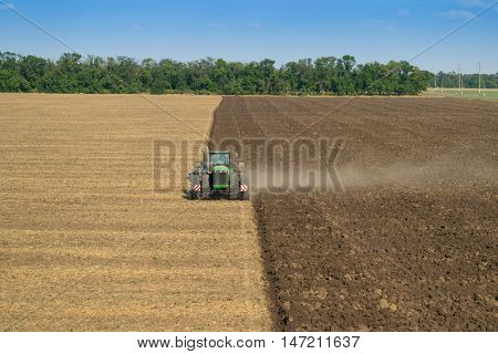 KRASNODAR REGION, RUSSIA - AUG 19, 2015: Modern green tractor plows big field, In 2015 in Krasnodar region yields reached record level - 58.4 centners per hectare