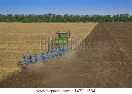 KRASNODAR REGION, RUSSIA - AUG 19, 2015: Tractor in dust plow big field, In 2015 in Krasnodar region yields reached record level - 58.4 centners per hectare