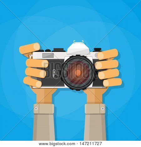 Hands holding photo camera. vector illustration in flat style on blue background