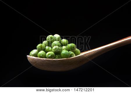 Peas on a spoon. A close up image of green peas on a wooden spoon.