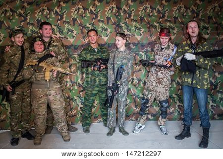 RUSSIA, MOSCOW - DEC 21, 2014: Men and women in camouflage with gun posing for photos in game laser tag.