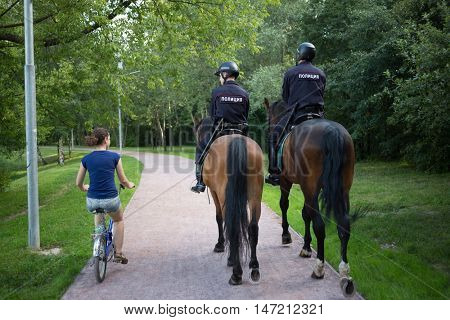 RUSSIA, MOSCOW - JUL 6, 2015: Back of two horse policemen and woman (model with release) rides bike in park at Sokolniki park.