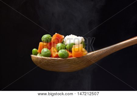 Steaming peas and carrots. Peas and carrots topped with butter on a wooden spoon with steam from below.