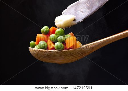 Peas and carrots topped with butter on a wooden spoon with steam from below.