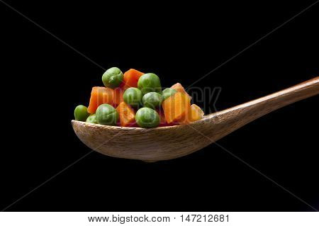 Mixed vegetables on wooden spoon. Peas and carrots on a wooden spoon with steam from below.