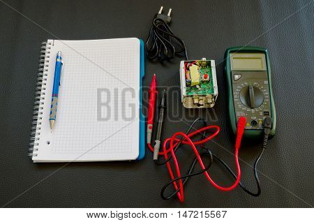 Amplification device with a testing unit and a notebook with pencil for notes