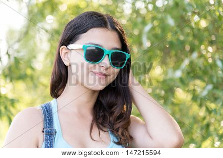 Portrait of teen girl in sunglasses on a nature summer
