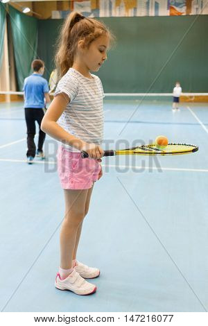 young female tennis player on tennis court holding racquet with ball, in gym