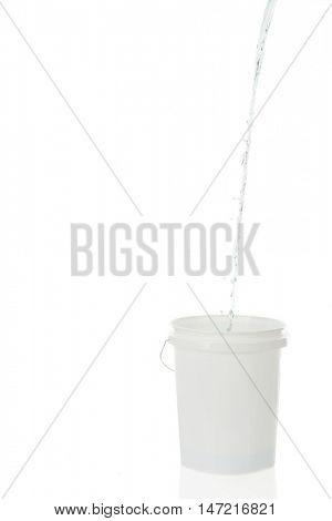High key image of water from an unknown source streaming into a white plastic bucket.  On a white background with plenty of space on the left for your text.