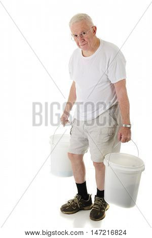 A senior man hunched and looking at the viewer as he carries two white buckets.  On a white background.