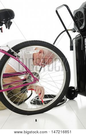 A senior man filling his granddaughter's bike tire, and air compressor nearby.  On a white background.