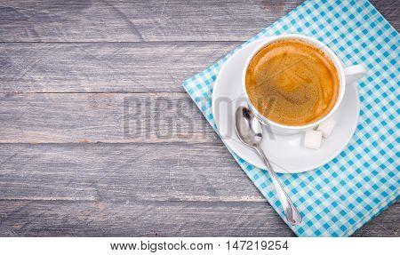 Cup of hot morning coffee on saucer with sugar and spoon on wooden board in rustic style