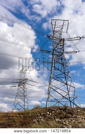 Electric power high voltage transmission line pylon tower on blue sky and white cloud background