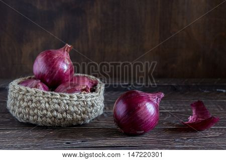 Jute basket with red onion onion on a brown background basket made of jute