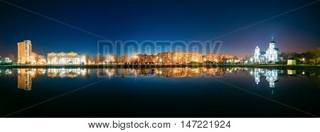 Panorama Of Night View Of Alexander Nevsky Orthodox Temple Church Behind City Lake. Evening Illumination Of Residential Area And Park Reflecting In Water Surface. The Early Spring In Gomel Homiel Belarus