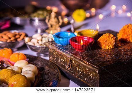 oil lamp or diya with crackers, sweet or mithai, dry fruits, indian currency notes, marigold flower and statue of Goddess Laxmi on diwali night while laxmi pujan or pooja