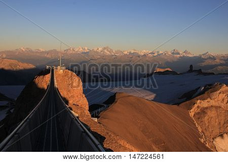 Evening scene on the Glacier de Diablerets Swiss Alps. Suspension bridge connecting two mountain peaks. Glacier and high mountains.
