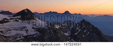 View from Glacier de Diablerets Swiss Alps. Colorful evening sky over high mountains. Silhouettes of Dents du Midi. Sunset. Summer scene.