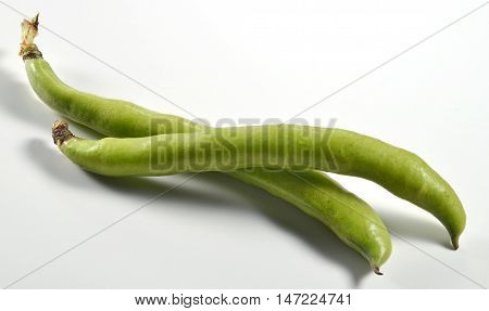 Two broad bean pods isolated on white board
