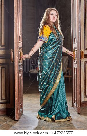 Woman in green with golden dress stands in doorway, holding doors handles.