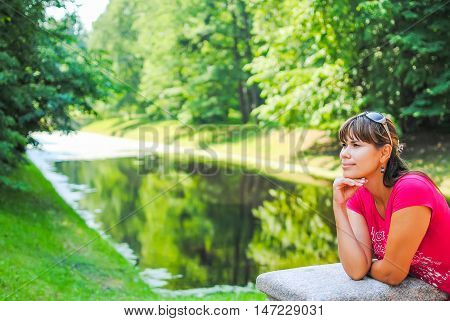 cute dreamy girl resting near the lake.