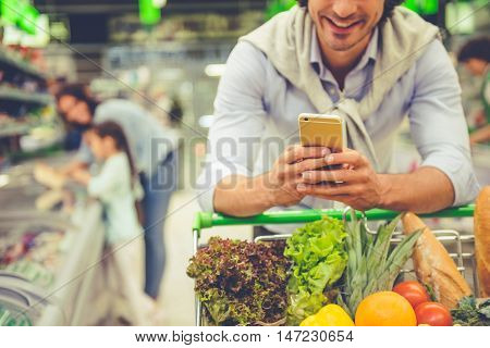 Family in the supermarket. Cropped image of dad leaning on shopping cart using a mobile phone and smiling in the background his wife and daughter are choosing food