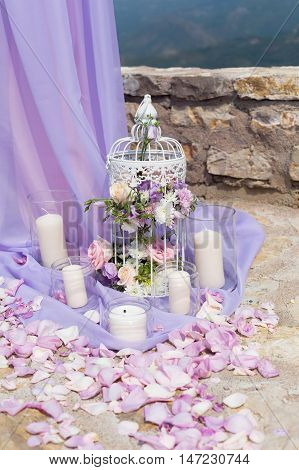 White cage with natural roses as decoration on wedding
