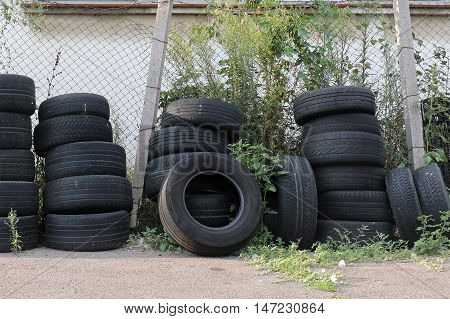Large pile of old used car tyres in thicket outside