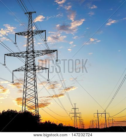 Electricity Pylon - standard overhead power line transmission tower at sunset