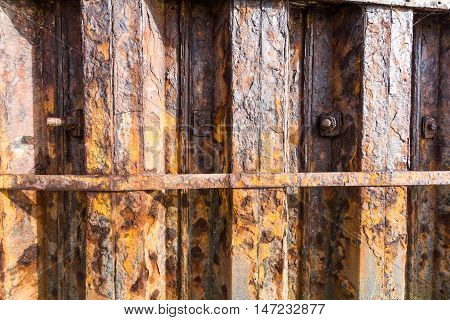 Rusting iron interlocked girders that form part of harbour harbour wall.